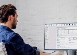 Homem sentado em frente a um computador utilizando o software S4
